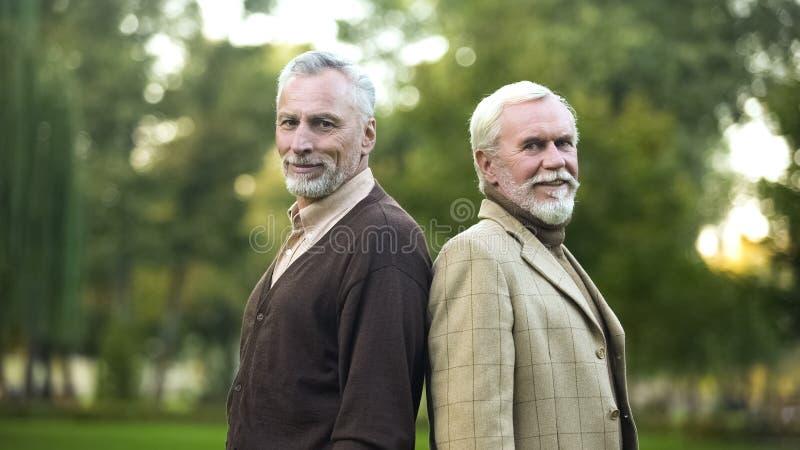 Уверенные пенсионеры стоя спиной к спине и усмехаясь для камеры, товар стоковое изображение rf