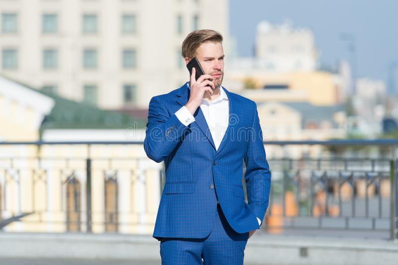 Уверенный бизнесмен говоря по телефону делать дело на движении бизнесмен с мобильным телефоном беспроводная связь стоковые фотографии rf