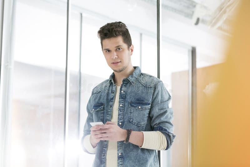 Уверенный бизнесмен отправляя SMS на смартфоне в офисе стоковые фото