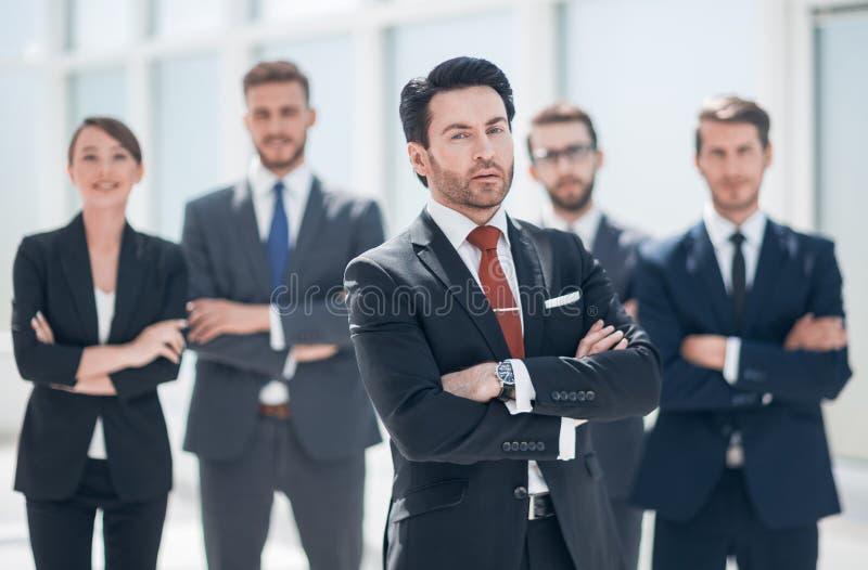 Уверенный бизнесмен перед его командой дела стоковое фото rf