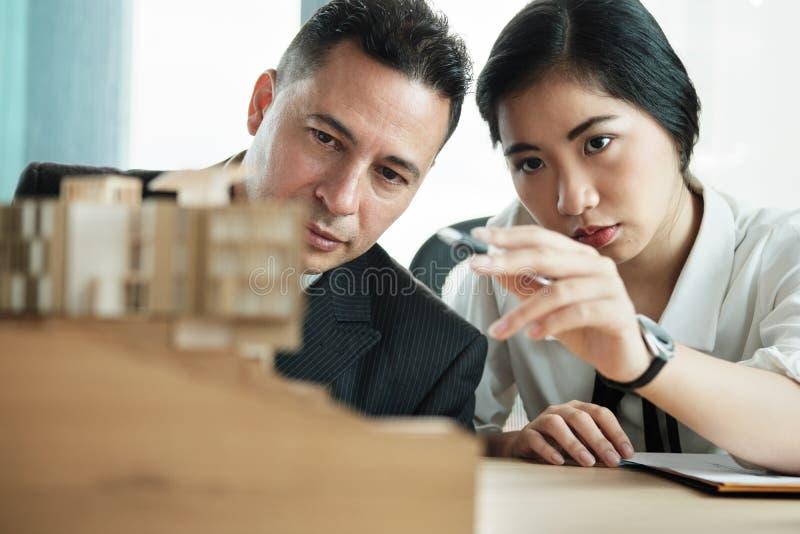 Уверенный бизнесмен смотря проект дома архитектуры миниатюрный стоковые изображения rf
