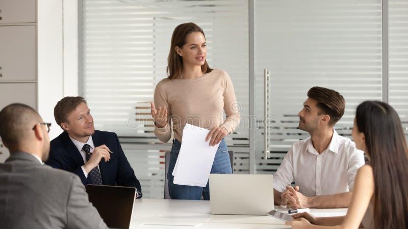 Уверенный женский менеджер представляя финансовый отчет говорит на встрече команды стоковые изображения