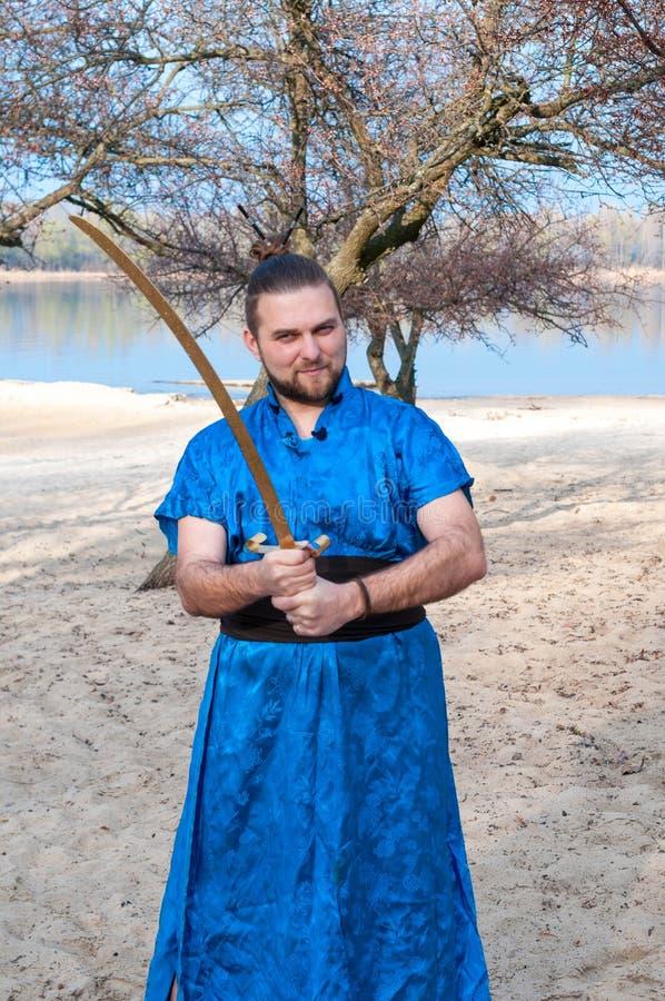 Уверенный красивый человек в голубом кимоно с плюшкой на шпаге удерживания головы стоковое фото