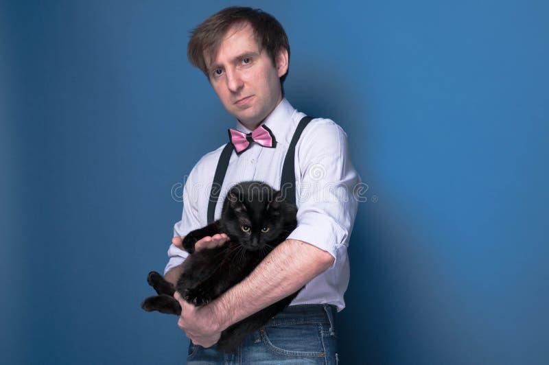 Уверенный красивый человек в рубашке, подтяжк и бабочке держа черного кота и смотря камеру стоковое фото