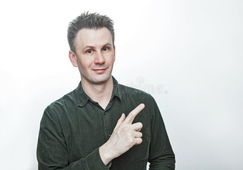 Уверенный молодой человек указывая палец в сторону на представление пустой рекламы космоса экземпляра невероятное, удивленный уди стоковое изображение