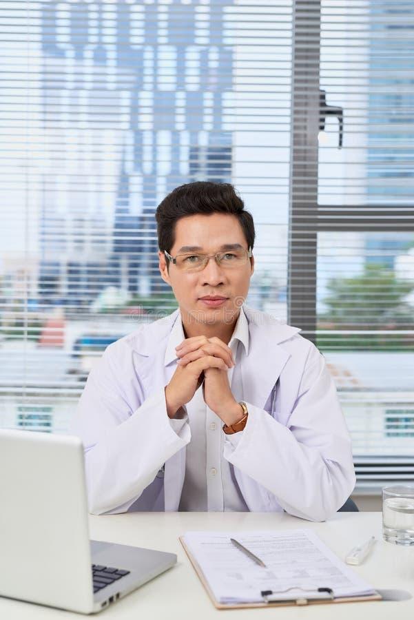 Уверенный мужской доктор с деятельностью стетоскопа в офисе стоковое фото
