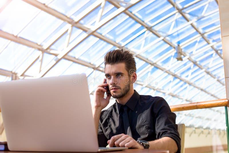 Уверенный мужской предприниматель вызывая через мобильный телефон стоковые изображения