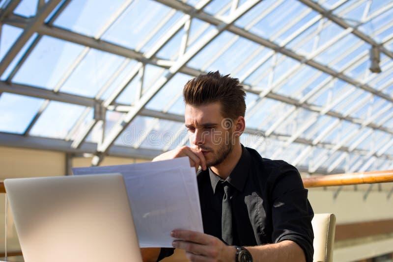 Уверенный мужской профессиональный работодатель читая печатные документы с контрактом стоковая фотография rf
