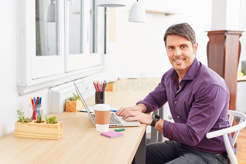 Уверенный основатель запуска на ноутбуке стоковая фотография