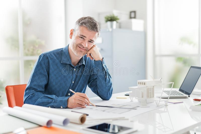 Уверенный профессиональный архитектор представляя в его офисе и усмехаясь на камере, он сидит на столе и работает на здании стоковое фото