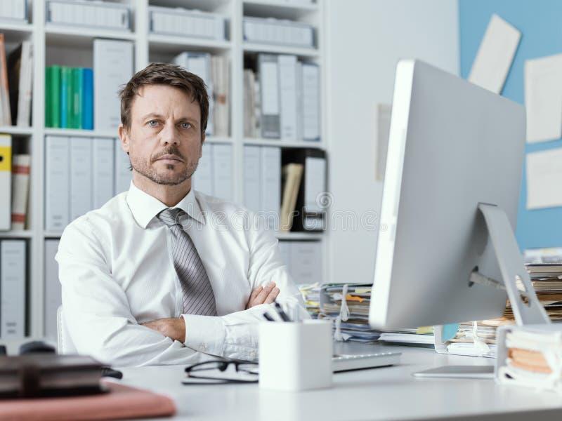 Уверенный руководитель бизнеса работая в офисе стоковое фото