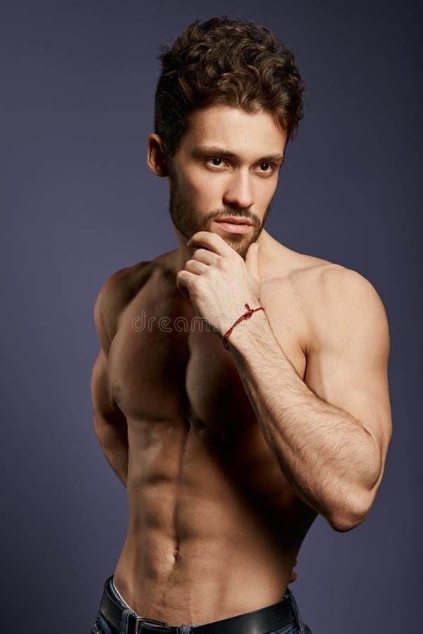 Уверенный серьезный без рубашки человек показывая обнаженное тело стоковое изображение rf