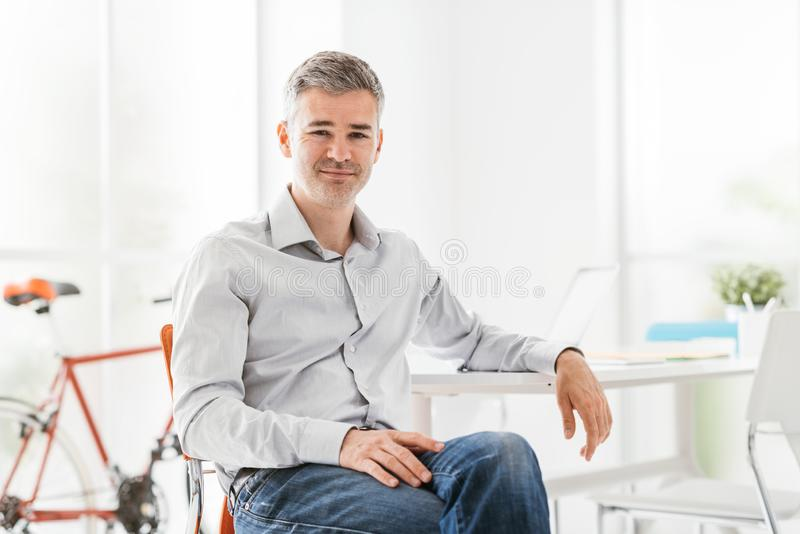 Уверенный современный бизнесмен сидя в его офисе и усмехаясь на камере стоковая фотография