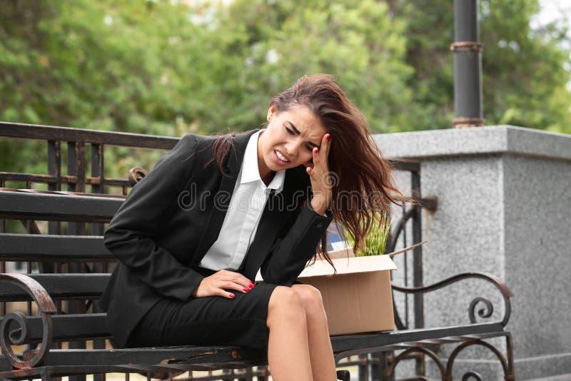Увольнятьый работник офиса с личным веществом сидя на стенде outdoors стоковое фото