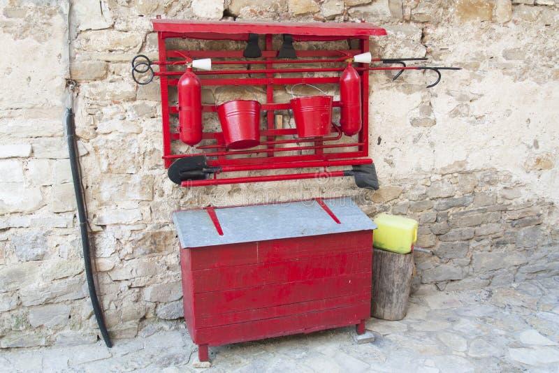 Увольняйте против ретро старой красной оси, лопаткоулавливателя, ведер Фото оборудования пожаротушения стоковые изображения rf