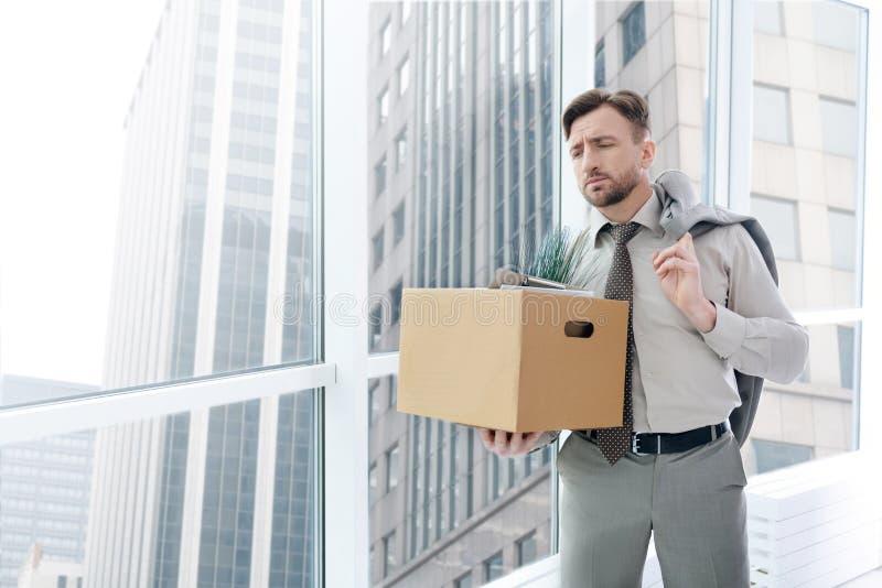 Увольнянный хмурый человек стоя в офисе стоковые фотографии rf