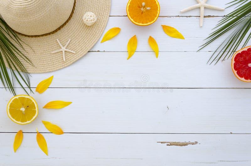 Угловая рамка аранжированная шляпой лета, тропическая ладонь выходит, свежие цитрусовые фрукты, seastones на белой деревянной пре стоковое изображение rf