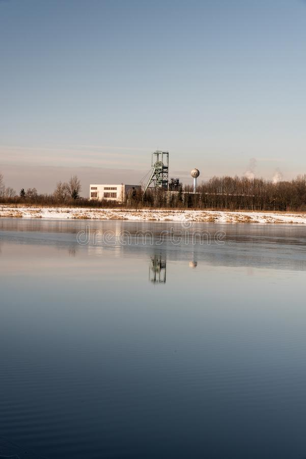 Угольная шахта жирного каменного угля Headframe od Ful Darkov отражая на fround воды Karvinske больше озера около города Karvina  стоковое фото