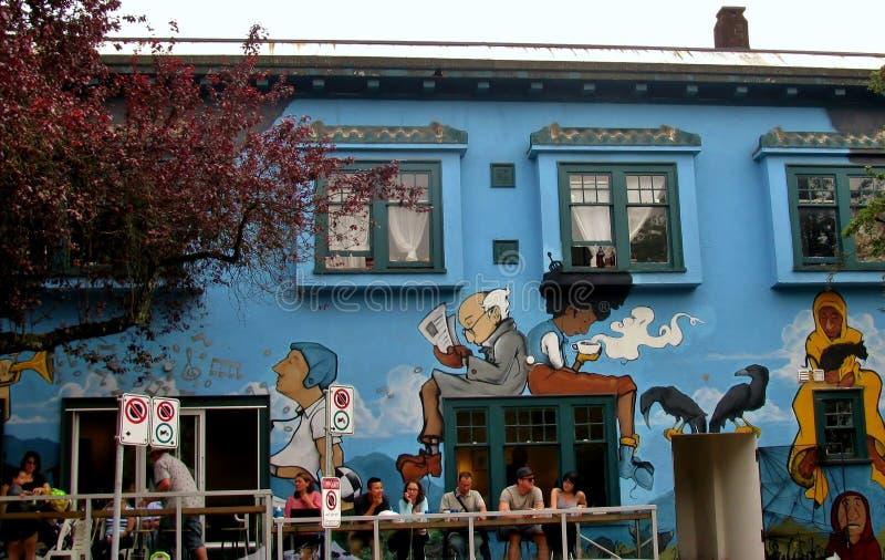 Угол коммерчески привода и улицы Чарльза, людей ослабляет над напитками под покрашенной настенной росписью Канада vancouver стоковые изображения