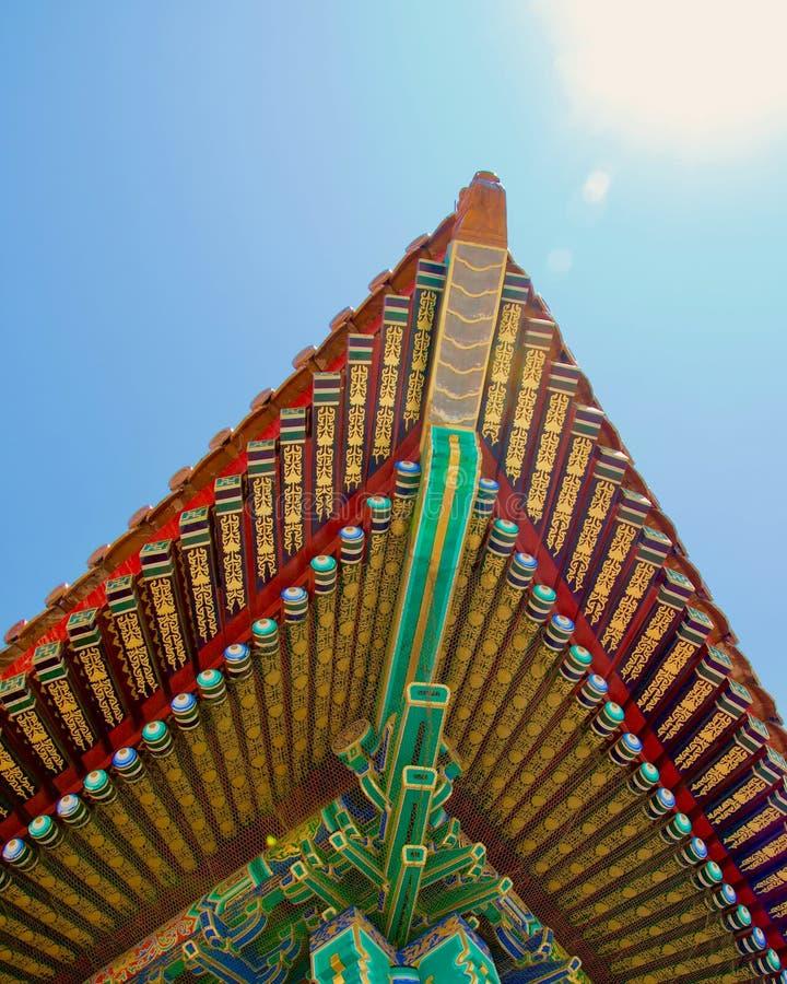 Угол крыши китайского здания: покрашенный в ярких цветах стоковое фото rf