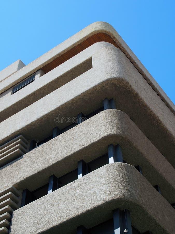 Угол многоквартирного дома brutalist конкретного конкретного с текстурированными округленными углами против голубого неба стоковые изображения rf