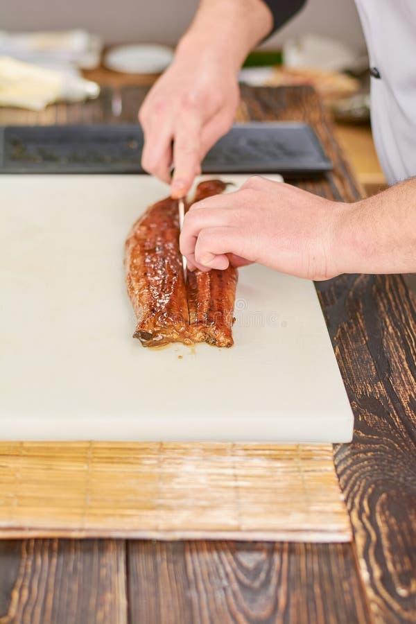 Угорь вырезывания кашевара на деревянном столе стоковая фотография rf