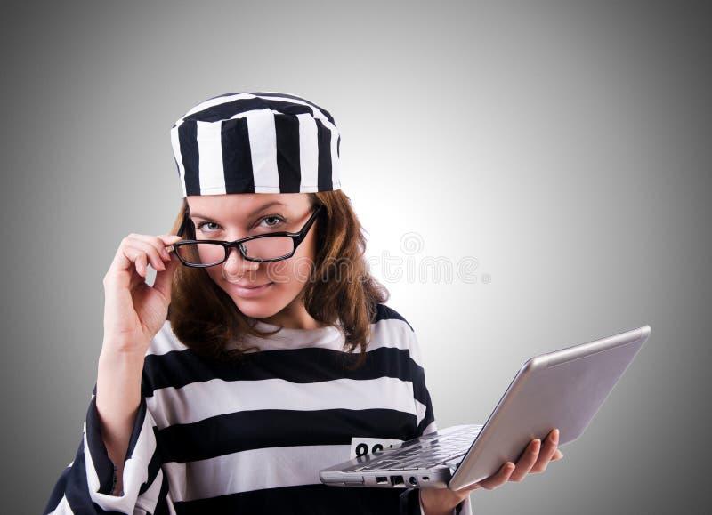 Уголовный хакер с компьтер-книжкой против градиента стоковые фото