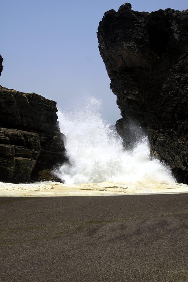 Угрожая опасная белая дамба отжимая через зазор утеса на черном пляже песка лавы на Тихом Океане стоковая фотография