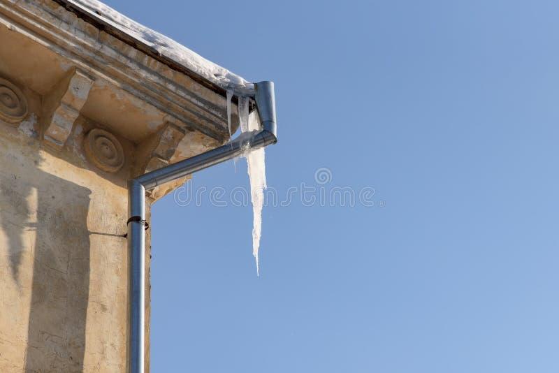 Угрозы зимы: сосульки висят от крыши здания Опасность для проезжих, угроза смерти и ушиб от сосулек стоковые фото