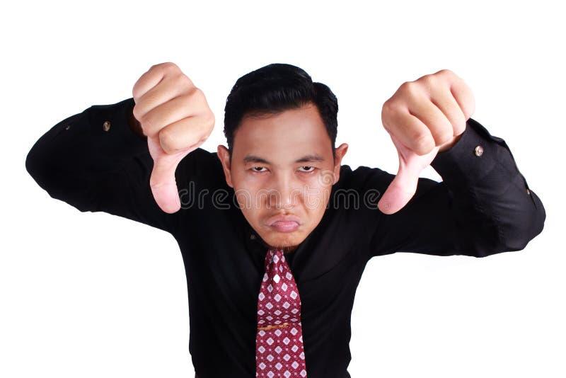 Угрюмый бизнесмен показывает большие пальцы руки вниз стоковые фото