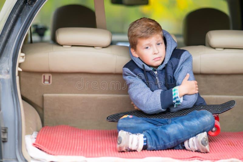 Угрюмый мальчик сидя в ботинке автомобиля стоковое фото rf