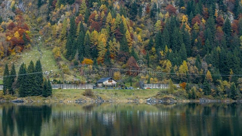 Удаленное здание и красочные деревья отразили в высокогорном озере Aut стоковое фото rf