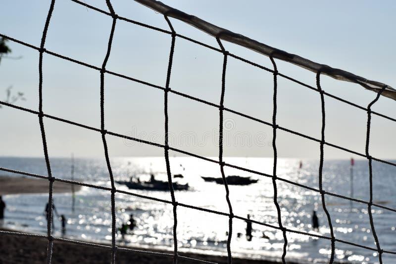 Ударять шарик сетчатый затемните взгляд людей купая на море селективный фокус, стоковое фото rf