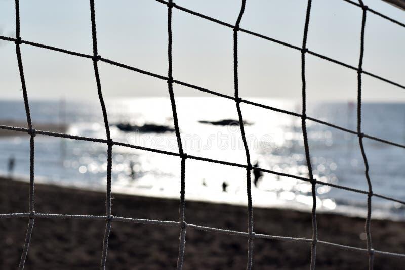 Ударять шарик сетчатый затемните взгляд людей купая на море селективный фокус, стоковое изображение rf