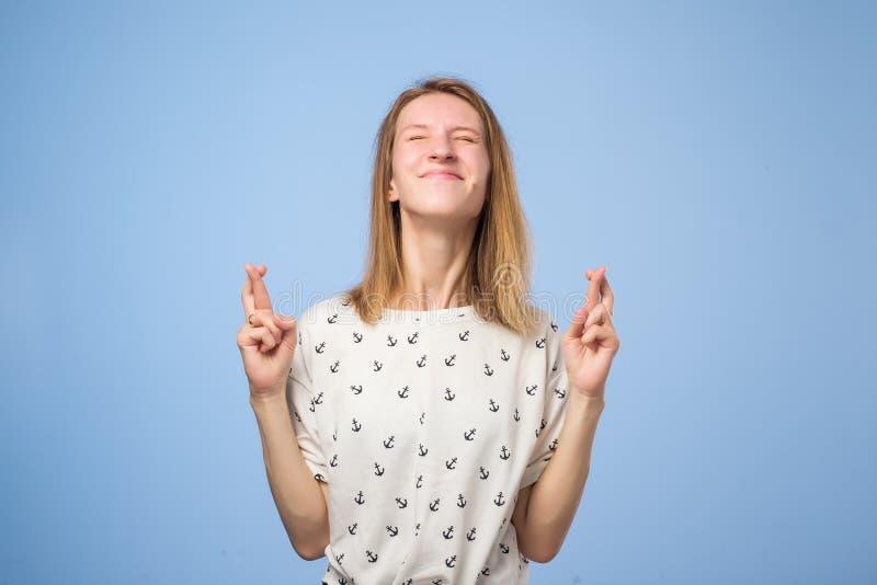 Удачливая красивая европейская женщина пересекает пальцы, надеется что все желания приходят верно стоковое фото rf