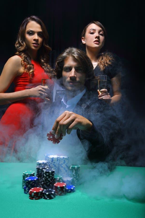 Удачный картежник окруженный обольстительными элегантными женщинами стоковое фото