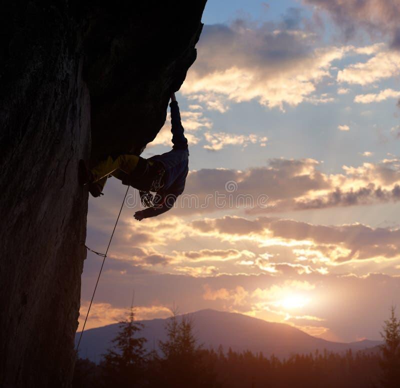 Удерживание альпиниста с одной рукой на вися утесе на восходе солнца в горах Весьма скалолазание Облачное небо с космосом экземпл стоковые фото