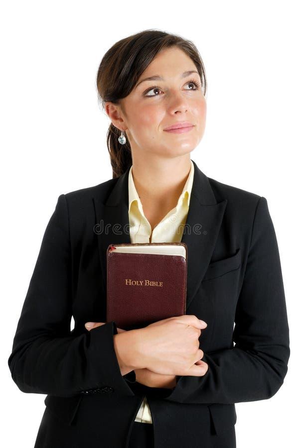 удерживание библии смотря вверх пока детеныши женщины стоковая фотография
