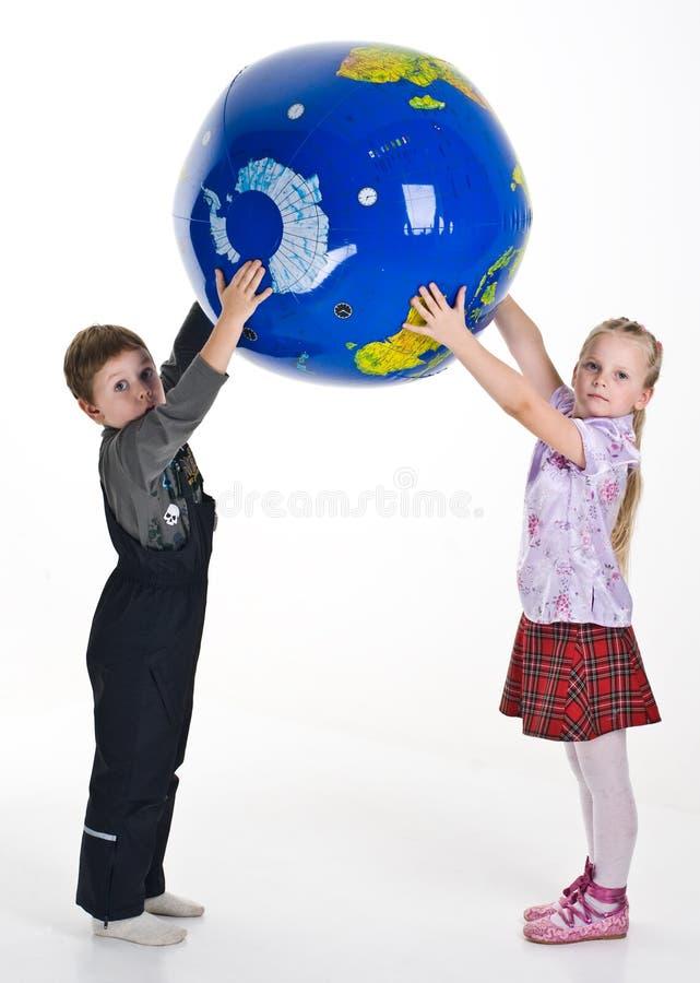 удерживание глобуса девушки мальчика стоковое фото rf