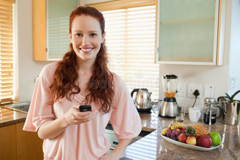 Удерживание женщины ее мобильный телефон в кухне стоковая фотография