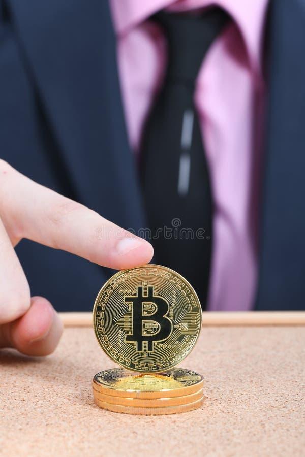 Удерживание золотое Bitcoin руки человека на коричневой текстурированной предпосылке пробочки стоковое фото rf
