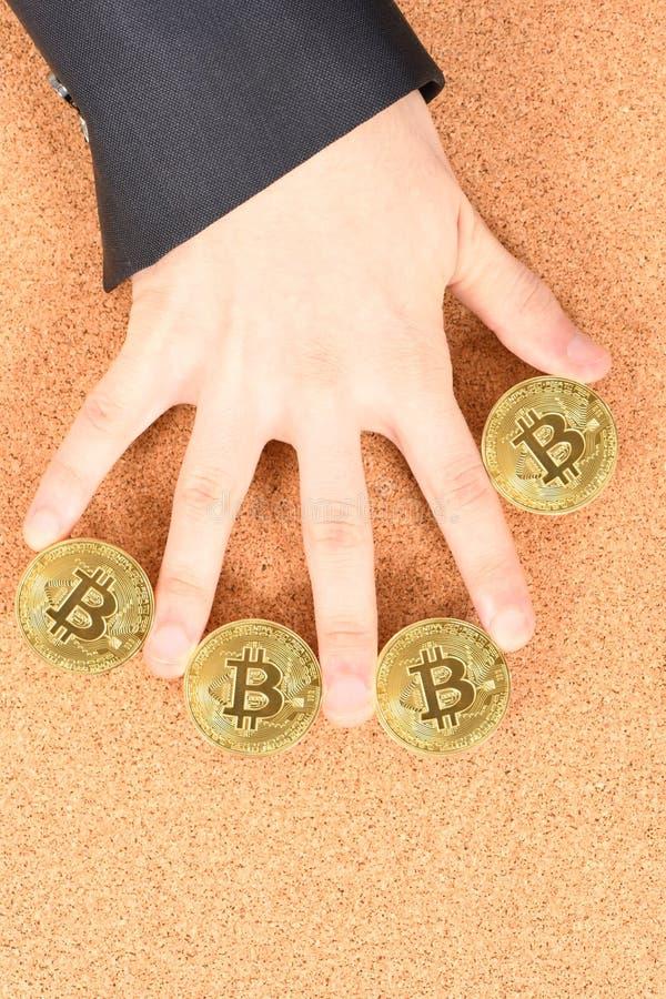 Удерживание золотое Bitcoin руки человека на коричневой текстурированной предпосылке пробочки стоковое фото