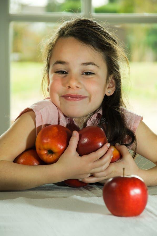 удерживание коричневого ребенка яблок с волосами стоковая фотография