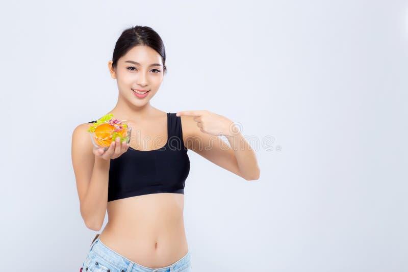 Удерживание красивой женщины портрета молодой азиатской усмехаясь и указывать еда овоща салата изолированная на белой предпосылке стоковое фото
