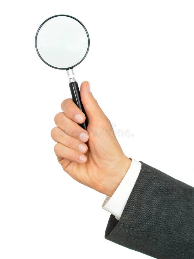 удерживание руки бизнесмена стеклянное увеличивая s стоковые фото