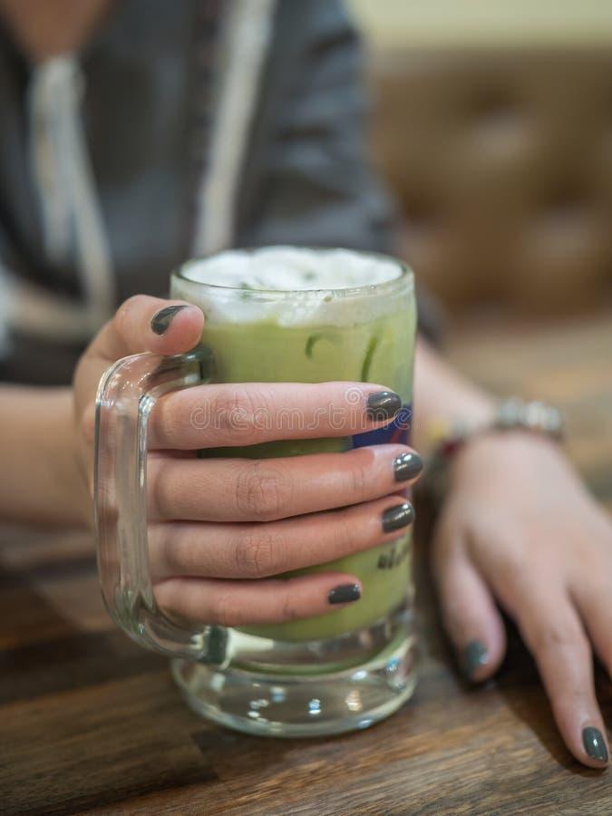 Удерживание руки женщины заморозило зеленый чай стоковая фотография