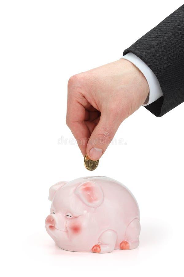 удерживание руки монетки банка над piggy стоковая фотография rf