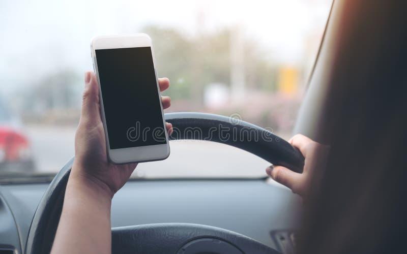 Удерживание руки ` s женщины и использование белого мобильного телефона с пустым черным экраном настольного компьютера пока управ стоковые изображения rf