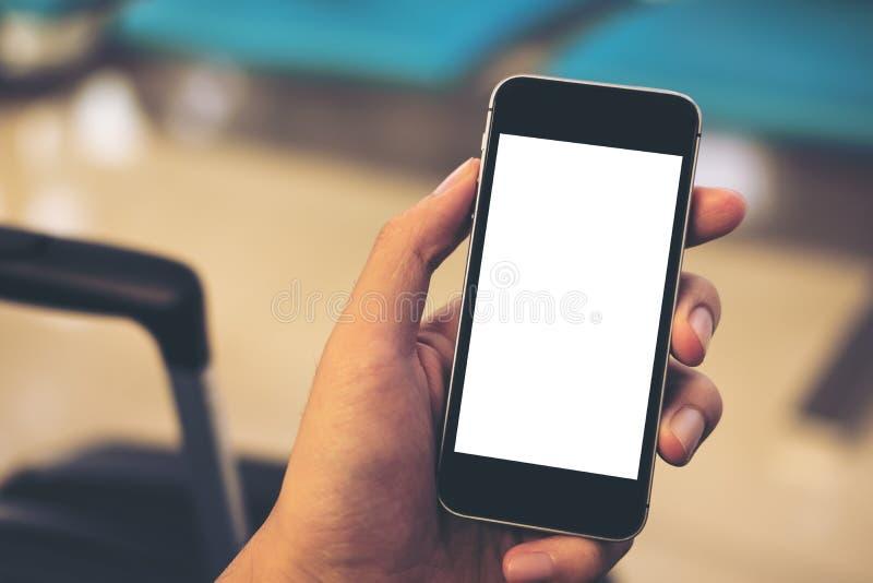 Удерживание руки ` s человека и использование черного мобильного телефона с пустым белым экраном с черным багажем в авиапорте стоковая фотография