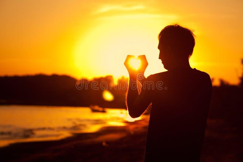 Удерживание человека в руках заходящее солнце стоковые изображения